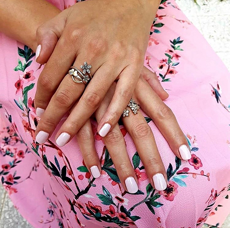 Woman with a pretty pink shellac manicure wearing a floral prom dress